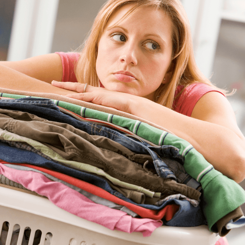 woman looking frustrated with a huge pile of laundry