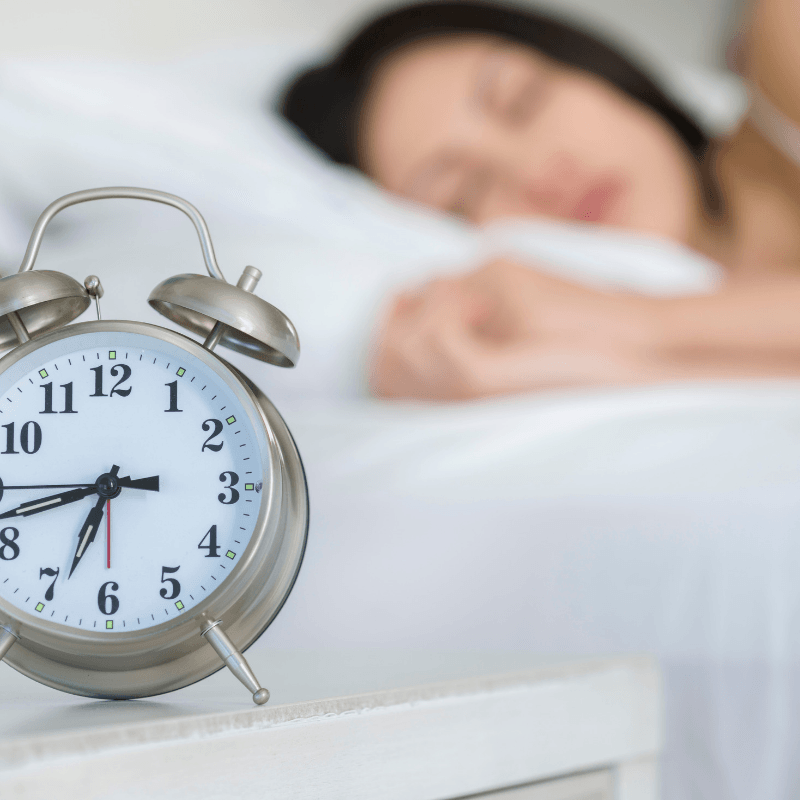 woman sleeping with an alarm clock to stay of schedule
